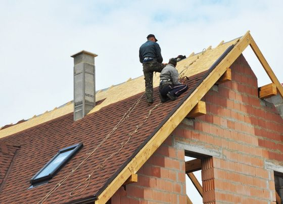 Two roofers working on a residential roof
